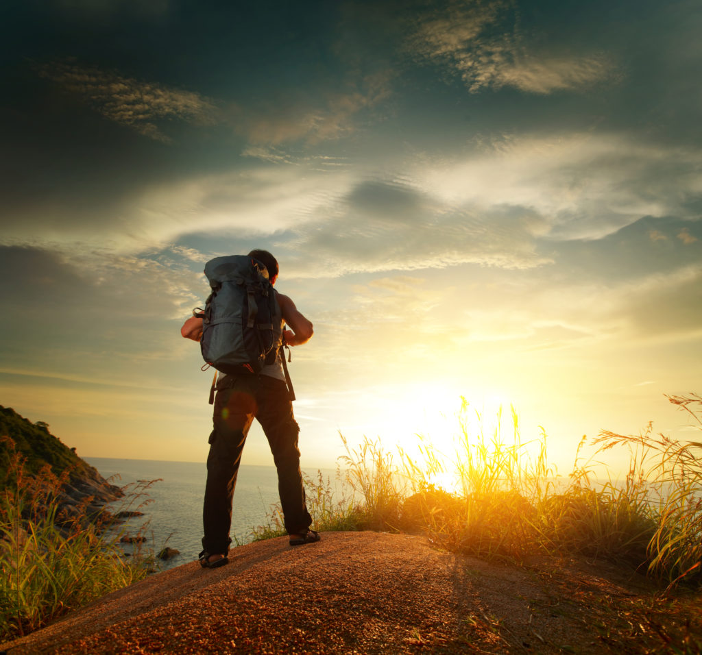 Hiker with internal frame backpack standing on a rock