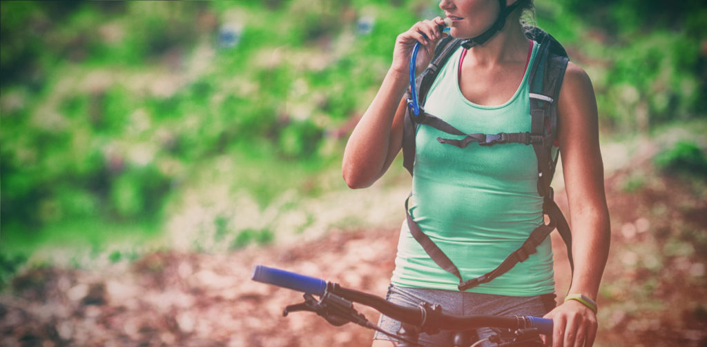 Female athlete drinking water from hydration pack in forest